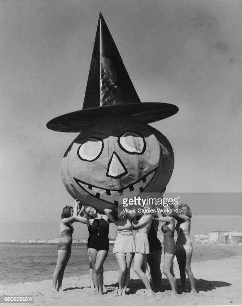 In advance of Halloween a group of young women in swimsuit pose on the beach a massive papier mache pumpkin in a witch's hat hoisted over their heads...