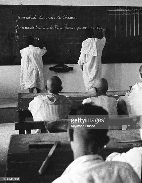 """In Algeria around 1950, in a colonial school classroom, two children writing on the board: """"I would like to see France when I am grown up"""". In a..."""