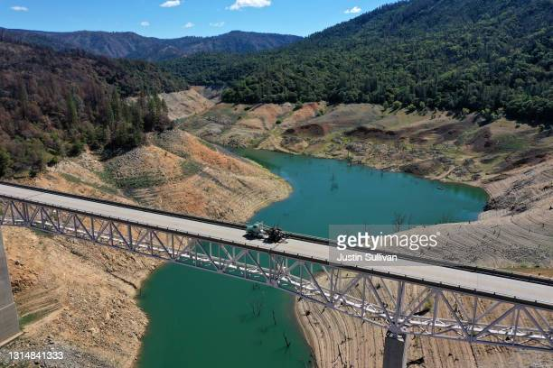 In an aerial view, a truck drives on the Enterprise Bridge over a section of Lake Oroville on April 27, 2021 in Oroville, California. Four years...