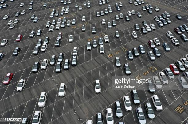 In an aerial view, brand new Subaru cars sit in half empty storage lot at Auto Warehouse Co. On May 14, 2021 in Richmond, California. New cars are...