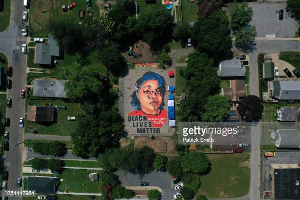 In an aerial view from a drone a largescale ground mural depicting Breonna Taylor with the text 'Black Lives Matter' is seen being painted at...