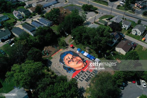 In an aerial view from a drone, a large-scale ground mural depicting Breonna Taylor with the text 'Black Lives Matter' is seen being painted at...