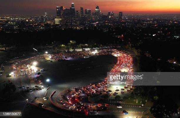 In an aerial view from a drone, cars are lined up at Dodger Stadium for COVID-19 testing as dusk falls over downtown on December 2, 2020 in Los...