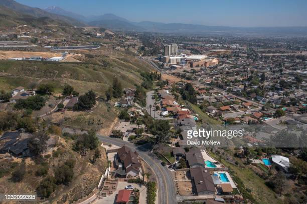 In an aerial view from a drone, the San Andreas Fault is viewed running directly under a street of a neighborhood built on the fault scarp and...