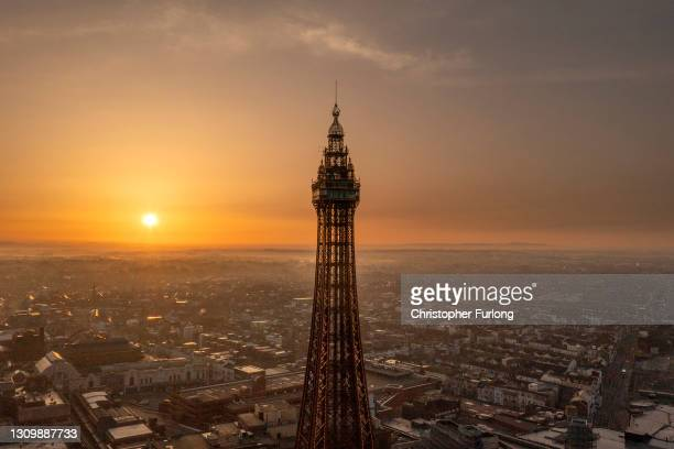 In an aerial view from a drone, the sun rises behind Blackpool Tower on March 30, 2021 in Blackpool, United Kingdom. Parts of the UK are set to see...