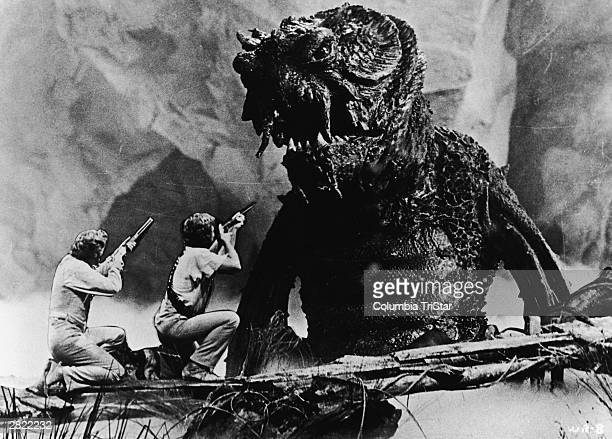 In an undersea cavern a monster from the depths threatens the cast of 'Warlords Of Atlantis' directed by Kevin Connor who fight back using rifles 1978
