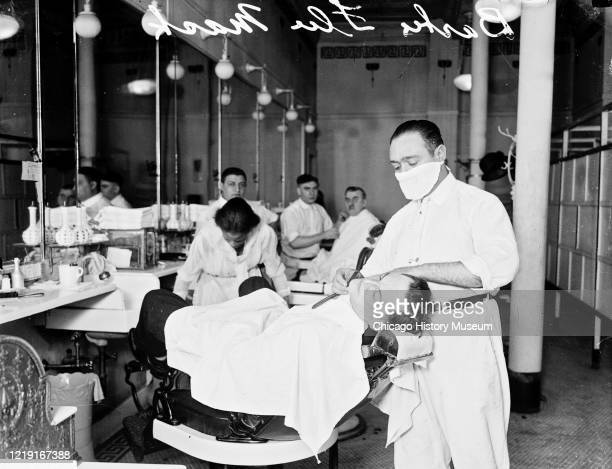 In an unspecified barbershop a man receives a shave from a barber in an influenza mask during the ongoing pandemic Chicago Illinois 1918