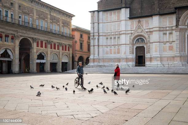 In an unusually empty Piazza Maggiore on March 13th 2020 in Bologna an encounter between a man and a woman is held keeping the safety distance...