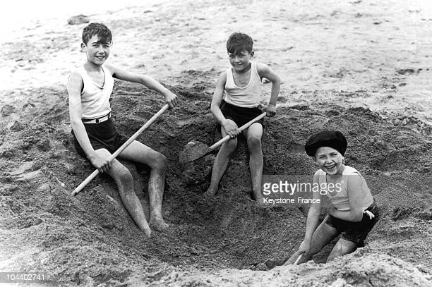 In August 1929, on Deauville beach, these three children dug a hole in the sand with shovels.