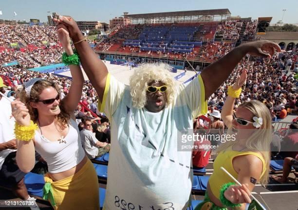 In ausgelassener Stimmung zeigen sich ein brasilianischer und zwei australische Fans am im Beach Volleyball Centre am Bondi Beach in Sydney beim...