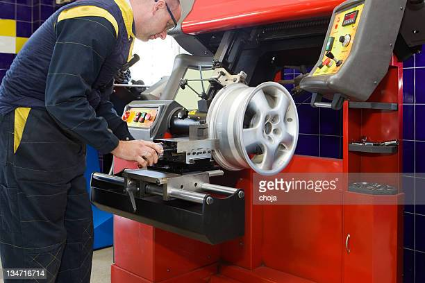 In auto repair shop....Auto mechanic is changin tire