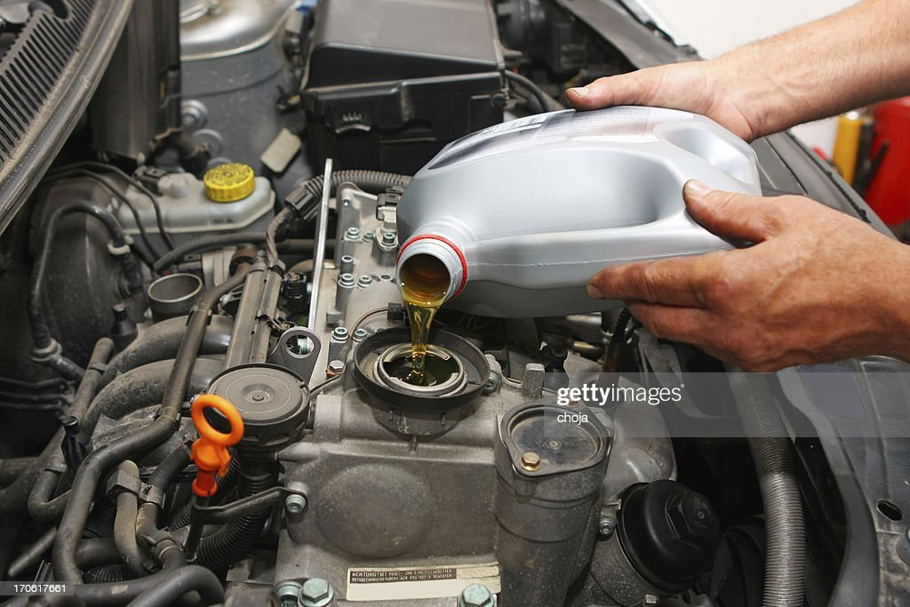 In auto repair shop...Car mechanic is changing engine oil : Stock Photo