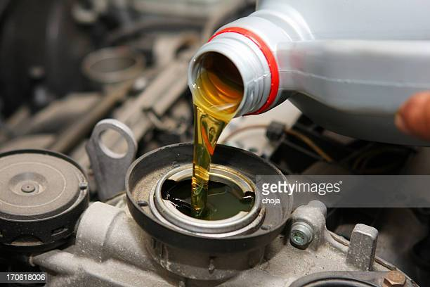 in auto repair shop...car mechanic is changing engine oil - motor oil stock pictures, royalty-free photos & images