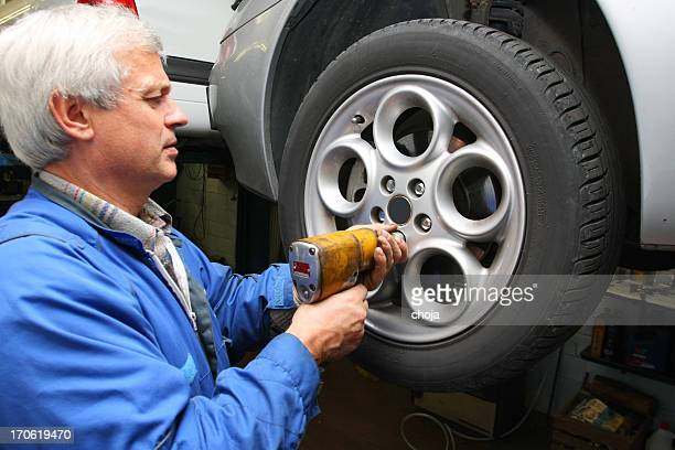 In auto repair shop...Car mechanic is changing tire