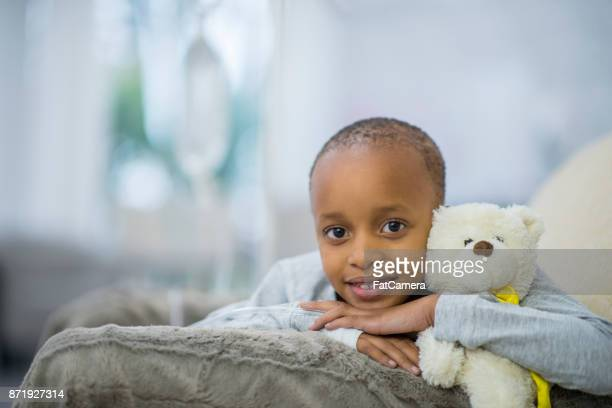 in bed with teddy - bald girl stock photos and pictures