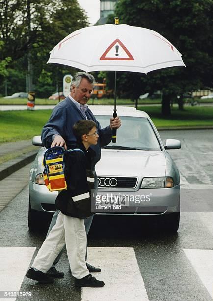 In Begleitung eines Erwachsenen überquert ein Kind einen Zebrastreifen. Der ältere Mann hält einen Schirm mit dem aufgedruckten Zeichen...