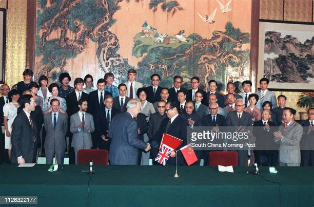 In Beijing the chairman of the Chinese negotiating team Zhou Nan andthe leader of the British Sir Richard Evans shake hands after signing the draft...
