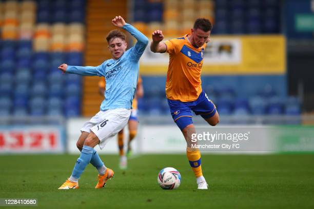 In Ben Knight of Manchester City action with Ollie Clarke of Mansfield Town during the EFL Trophy match between Mansfield Town and Manchester City...
