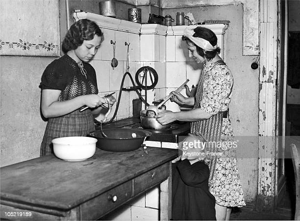 In Berlin On August 17 A Mother Prepares Potato Soup While Her Eldest Adolescent Daughter Peels Them And Her Youngest Daughter Looks On This Mother...