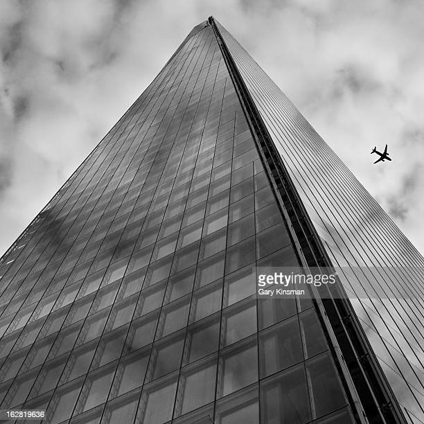 CONTENT] In black and white taken at the base of the Shard looking up as an plane flys past London Bridge London 2012