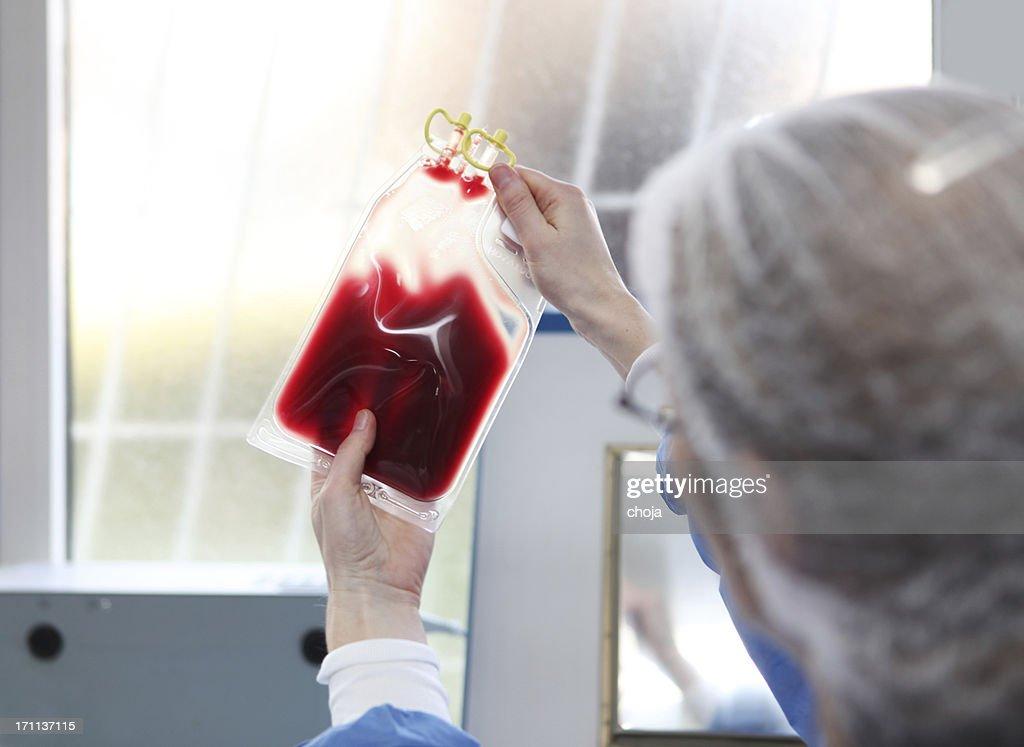 En sangre bank.Doctor en traje hazmat está revisando bolsa de sangre : Foto de stock