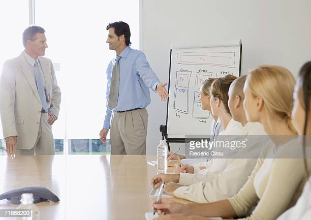 In boardroom, businessman introducing ceo to business team