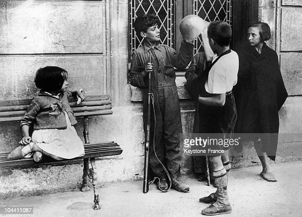 In Burgos during the Spanish civil war children are admiring the helmet and rifle of the elder brother signedup in Franco's troops