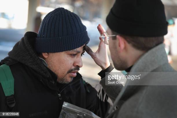 In celebration of Ash Wednesday Jonathan Randall Grant of the Urban Village Church rubs ashes on the forehead of a commuter outside of a subway...