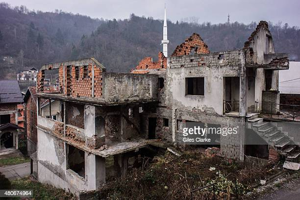 In central Srebrenica a new minaret from a mosque sprouts up behind a ruin from the war