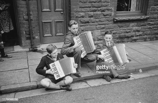 In centre a young school boy evacuated from an English city is taught how to play an accordian by two miners sons on the kerb of a street in a pit...