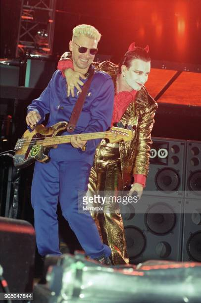 U2 in concert on the Zoo TV Tour Wembley Stadium Bono performing on stage Adam Clayton and Bobo on stage 11th August 1993