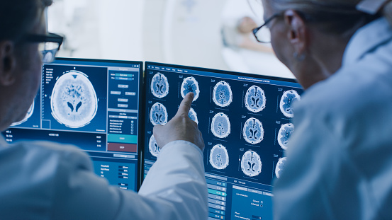 In Control Room Doctor and Radiologist Discuss Diagnosis while Watching Procedure and Monitors Showing Brain Scans Results, In the Background Patient Undergoes MRI or CT Scan Procedure. 1074166486