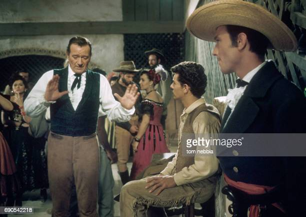 In costume American actor John Wayne directs actors Frankie Avalon and Laurence Harvey on the set of their film 'The Alamo' Brackettville Texas 1960