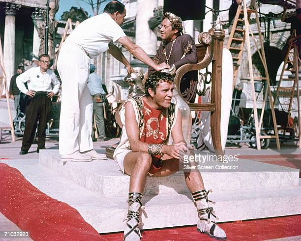 In costume for his role as as Marc Antony, Welsh actor Richard Burton , takes a cigarette break on the set of 'Cleopatra', directed by Joseph L....