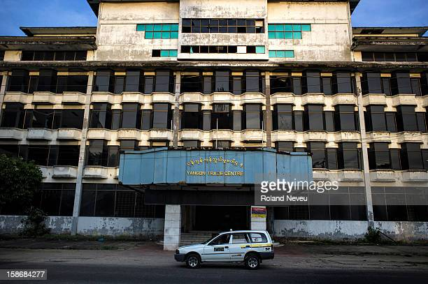 In downtown Yangon a taxi has park in front of the rundown and abandonned government trade office