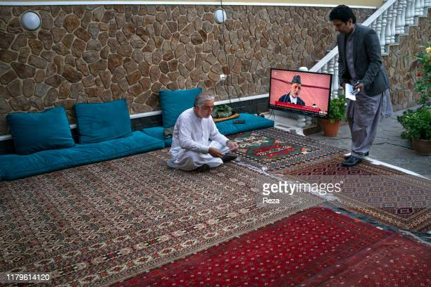In Dr Abdullah's house before he goes to the network TOLO to a debate, the candidate works his files while remaining informed of the news. On the...