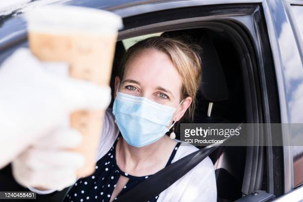 in drive-through, woman purchases hot coffee - drive through stock pictures, royalty-free photos & images
