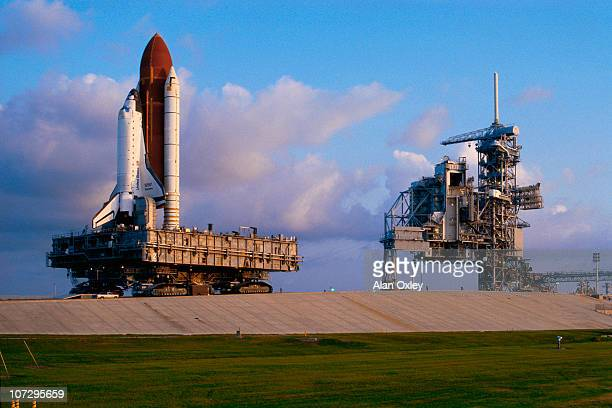 In early golden sunlight the Space Shuttle Discovery aboard its giant transporter crawls uphill toward launchpad 39B at the Kennedy Space Center in...