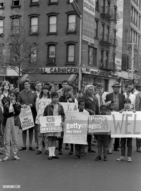 In East Harlem residents many with posters stand in an intersection to greet the arriving the Poor People's Campaign 1968 march East Harlem New York...