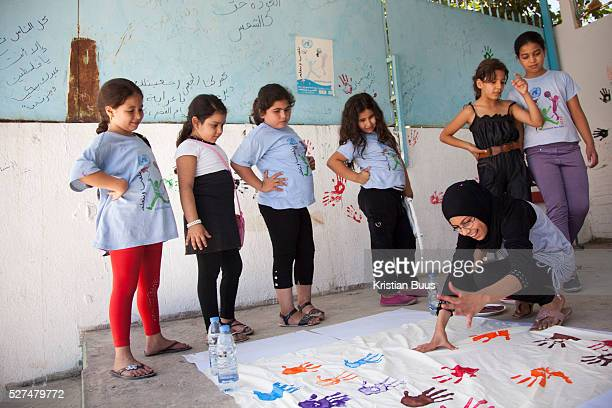In Ein ElHilweh refugee camp home to 75000 Palestinians Girls make a banner with their colorful hand prints It is summer break in the UNWRA school...