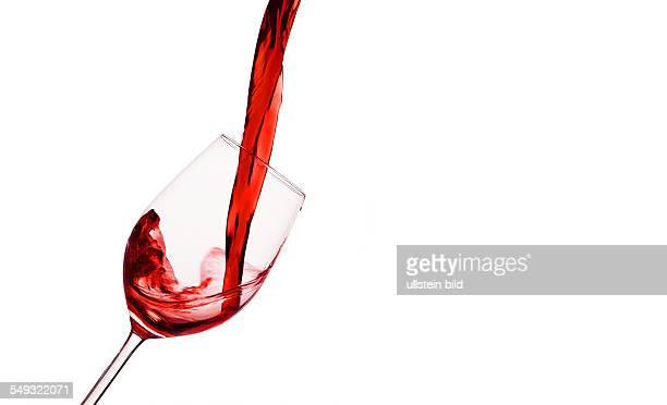 In ein Glas wird roter Wein eingegossen Rotwein im Rotweinglas