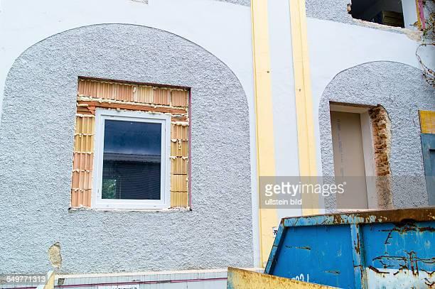 In einem alten Haus werden neue Fenster eingemauert Sanierung und Renovierung von alten Gebäuden