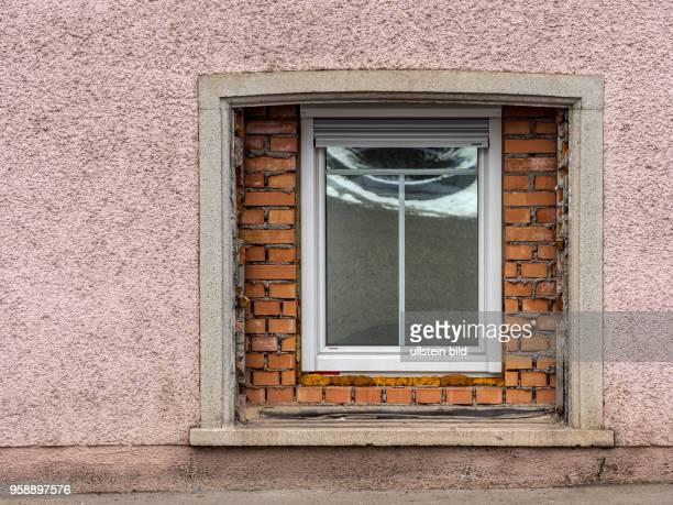 In einem alten Wohnhaus wurde ein großes Fenster durch ein Neues ersetzt Symbol für Althaussanierung und Wohnraumverbesserung