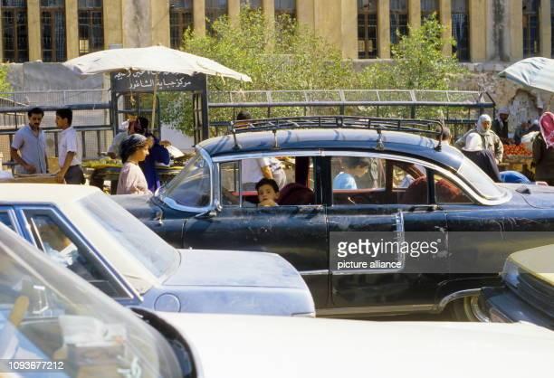 In einem am Straßenrand geparkten älteren Auto in Damaskus sitzt ein Junge am Steuer, so dass es aussieht, als ob er am Straßenverkehr teilnehmen...