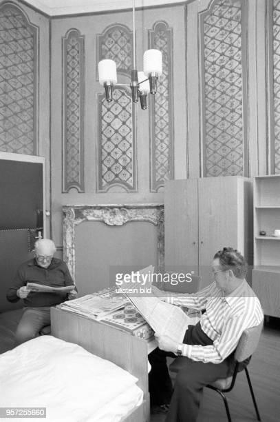 In einem Schlaf und Wohnraum mit Betten und Schränken sitzen zwei Männer und lesen Foto vom Die Männer sind Patienten im DiabetikerSanatorium Helmut...
