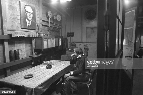 In einem tristen Raum mit Überwachungsschreibern, Manometer und Telefon sitzt ein Kesselwärter unter dem Porträt des DDR-Staatsratsvorsitzenden und...