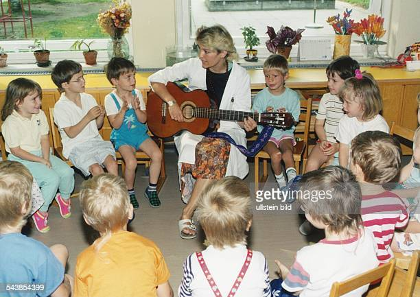 In einer Kindertagesstätte haben sich die Kinder im Kreis zusammengefunden und singen und musizieren miteinander Die Erzieherin spielt dazu Gitarre...