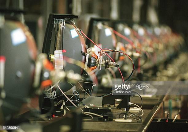 In einer Produktionsstraße der Firma Grundig stehen Fernsehgeräte mit offener Rückseite in einer Reihe Die Bildröhre der Geräte ist deutlich sichtbar