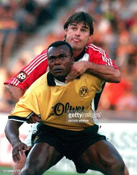 In Erwartung des Balles muß sich der togolesische Stürmer Bachirou Salou von Borussia Dortmund des harten Einsatzes des Stuttgarter Abwehrspielers...
