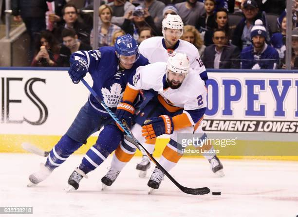 TORONTO ON FEBRUARY 14 In first period action Toronto Maple Leafs center Leo Komarov and New York Islanders defenseman Nick Leddy battle for the puck...